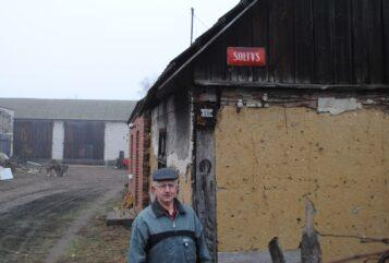 Sołtys Erazm Walkowiak przy swoim dawnym domu, na którym wciąż wisi tabliczka zawieszona w latach 70′