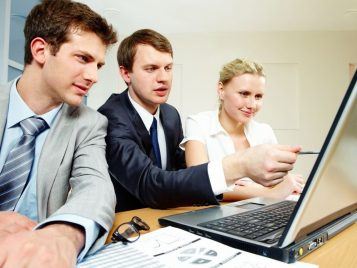 Pracownicy biurowi przy laptopie